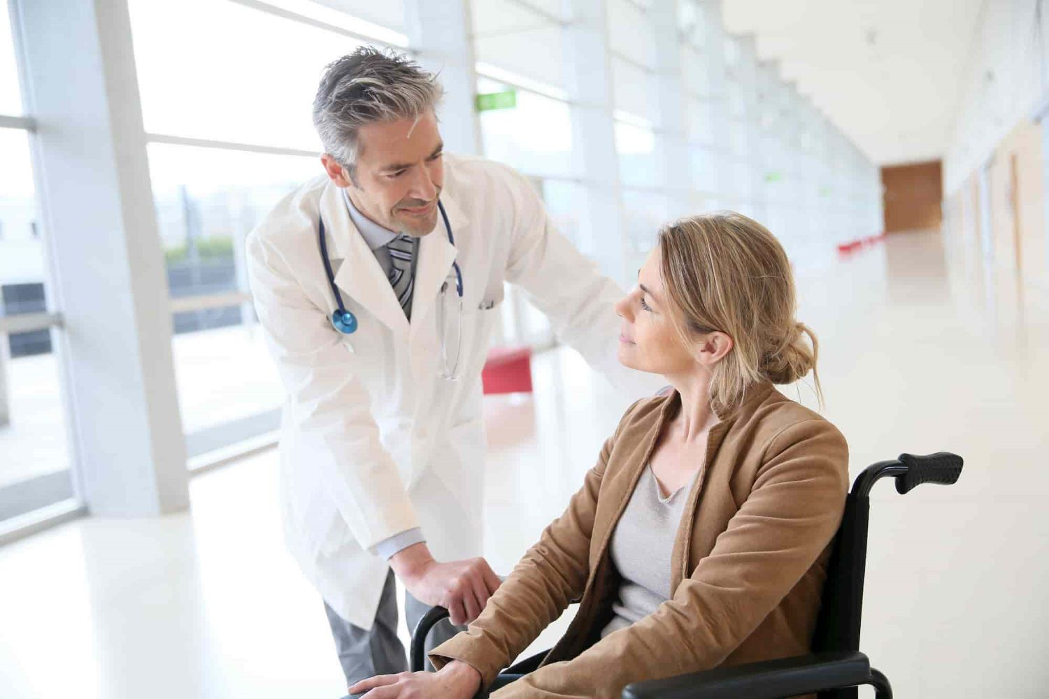A doctor talking to a patient in a wheelchair