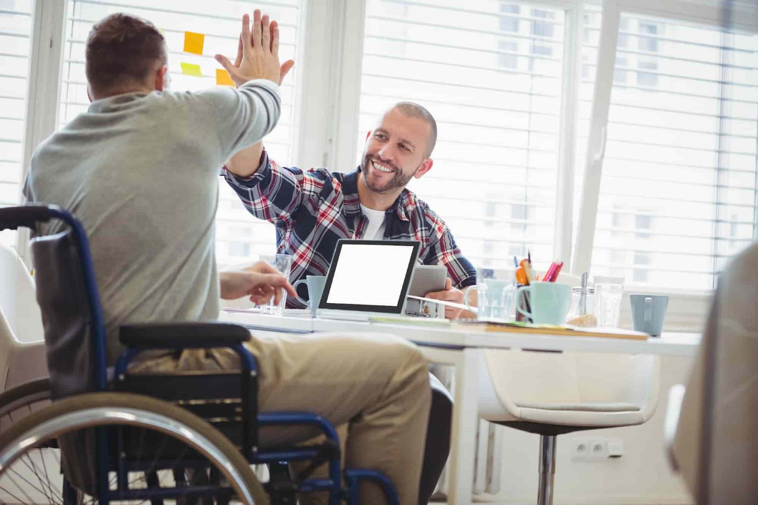 A man in a wheelchair and another man high fiving